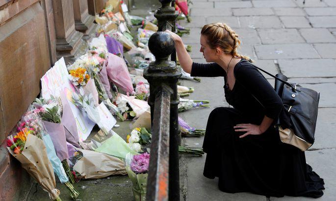 Trauer um die Opfer von Manchester. Eine Frau legt Blumen im Zentrum der britischen Stadt nieder und hält inne.
