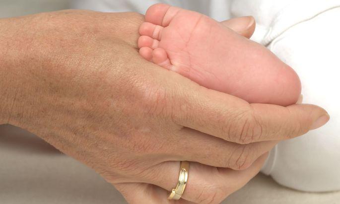 Symbolbild: Frauenhand und Babyfuß