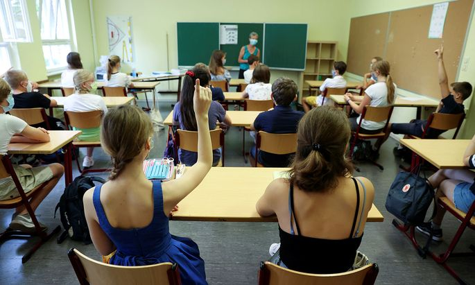 Pupils of the protestant high school ´Zum Grauen Kloster´ attend a lesson on the first day after the summer holidays in Berlin