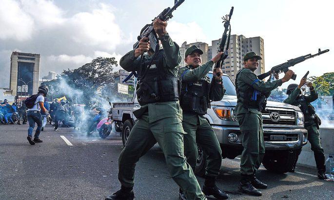 Teile der Nationalgarde, die sich Guaidó angeschlossen haben, vertreiben Maduro-treue Sicherheitskräfte vor der Militärbasis La Carlota.