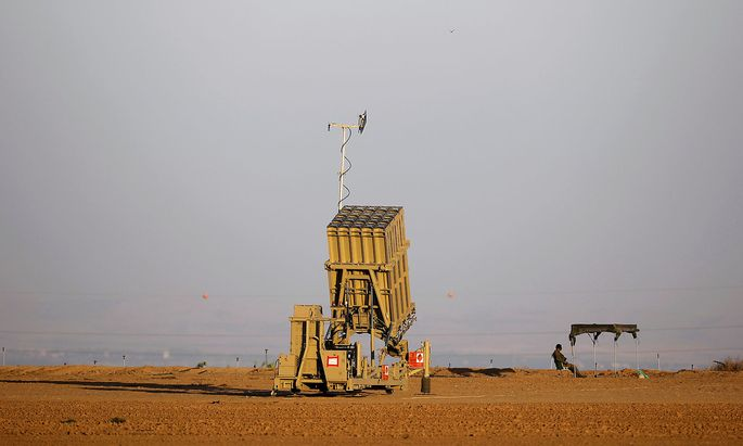 FILE PHOTO: An Israeli soldier keeps watch by an Iron Dome rocket interceptor battery deployed near central Gaza Strip
