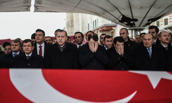 Der türkische Präsident, Erdoğan (2. v. l.), und der frühere Premier Ahmet Davutoğlu (l.) bei der Beerdigung eines der Polizisten, die beim Anschlag am Wochenende getötet worden sind.