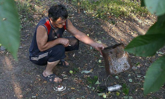 Ein Bewohner von Donetsk mit angeblichen Überresten von StreumunitionA local resident displays a dud unit of a cluster munition in Donetsk