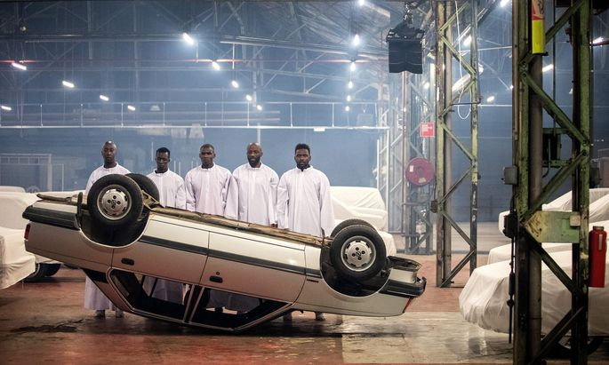Seltsam gekleidete Männer in einem unheimlichen Parkhaus mit einer Menge verhüllter Fahrzeuge: Wohin will uns Romeo Castellucci diesmal führen?