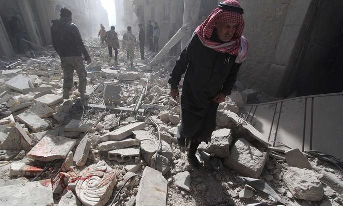 A man walks on debris, at a site hit by what activists said was a barrel bomb dropped by forces loyal to Syria´s President Bashar al-Assad, in the al-Myassar neighbourhood of Aleppo