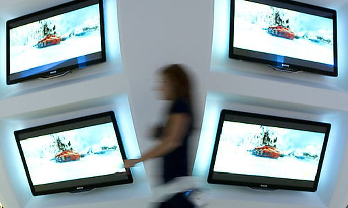 A woman walks in front of television screens of Philips in preparation of IFA, the worlds largest trs largest tr