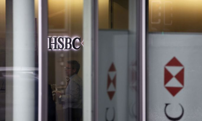 People are seen inside a HSBC Swiss branch of the bank in Geneva