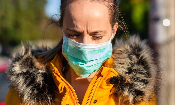 Woman wearing face mask because of air pollution in the city.