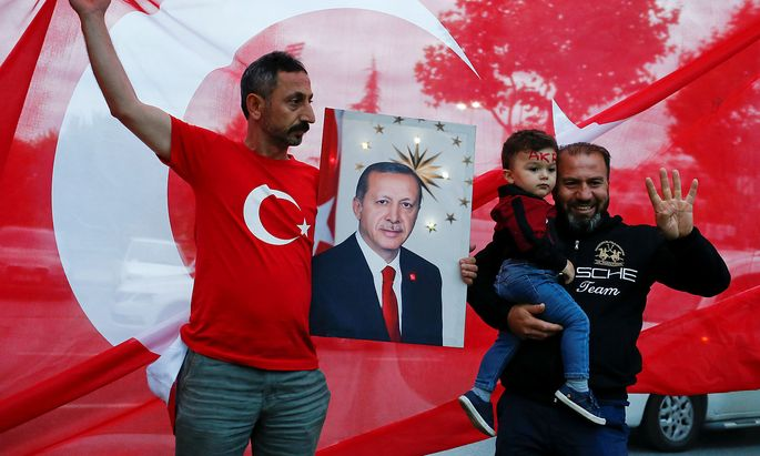 A supporter of AK Party holds a picture of Turkish President Tayyip Erdogan outside the party's headquarters in Istanbul