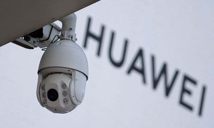 FILE PHOTO: A surveillance camera is seen next to a sign of Huawei in Beijing
