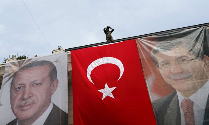 A special forces police officer takes security measures as he stands on top of a building where the portraits of Turkey´s President Erdogan, Prime Minister Davutoglu and a Turkish flag are displayed in Istanbul