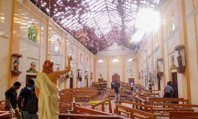 Crime scene officials inspect the site of a bomb blast inside St Sebastian´s Church in Negombo