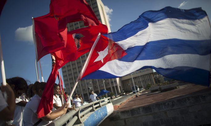 Students hold flags during a ceremony in Havana