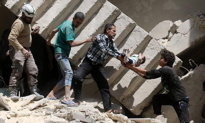 Helfer retten ein Baby aus den Trümmern eines Hauses.