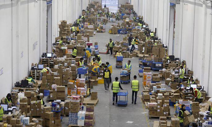 FILE PHOTO - Employees sort boxes and parcels at the logistic centre of a express delivery company, after the Singles Day online shopping festival, in Wuhan