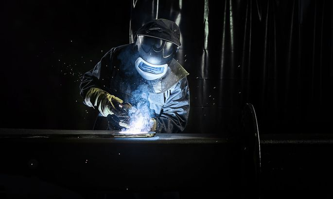 Industrial worker in protective clothing welding metal with welding torch