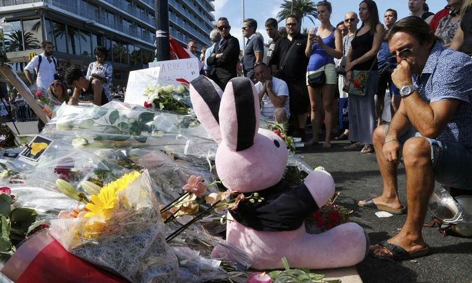 People gather near flowers, candles and a stuffed toy as they pay tribute near the scene where a truck ran into a crowd at high speed killing scores and injuring more who were celebrating the Bastille Day national holiday in Nice