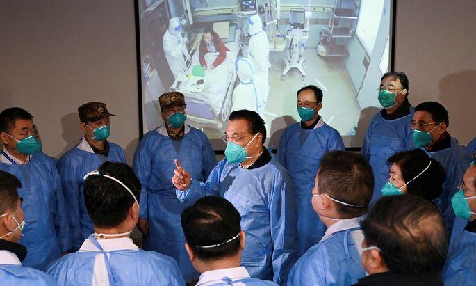 Chinas Premierminister Li Keqiang (Mitte) spricht in einem Krankenhaus in Wuhan zu Personal und Sicherheitskräften.