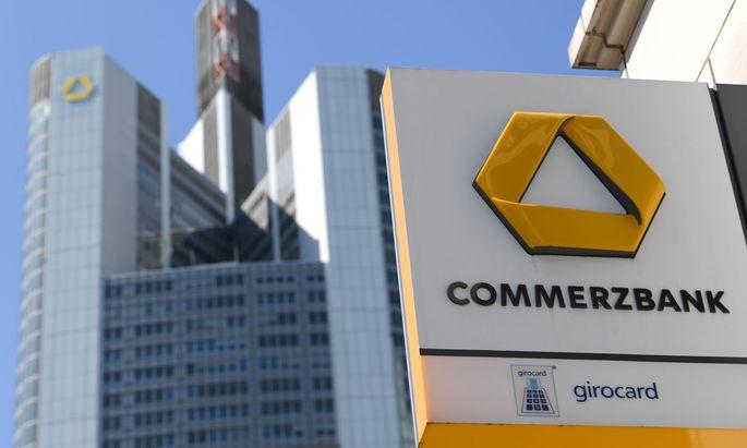 Gewinneinbruch wegen niedriger Zinsen und Kosten für Konzernumbau.