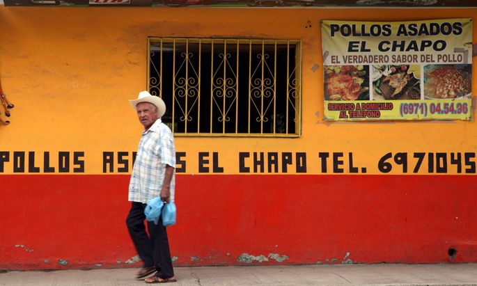 A resident walks past the ´Chapo´ roast chicken restaurant near the main plaza of Joaquin ´El Chapo´ Guzman´s hometown in the municipality of