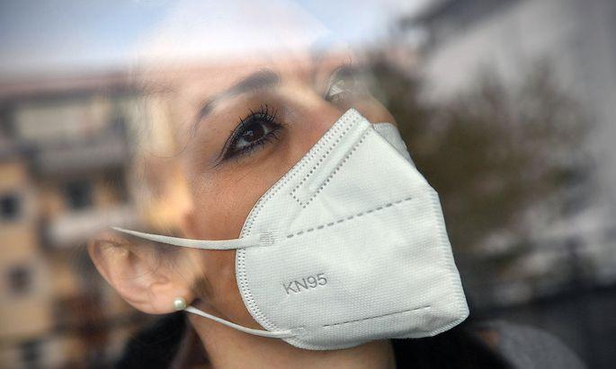 Themenbild Corona: Eine junge Frau mit Schutzmaske, Mundschutz,FFP2 KN95 medizinische Maske, Community Maske blickt sorg