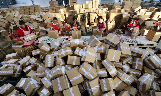 Chinesische Postmitarbeiter sortieren die Paketberge, die Alibaba am selbst erfundenen Singles' Day in die Welt schickt.