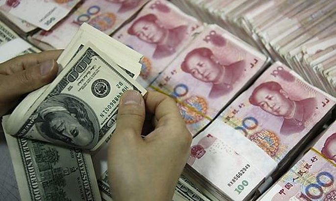 An employee counts U.S. dollar banknotes at a branch of the Industrial and Commercial Bank of China i