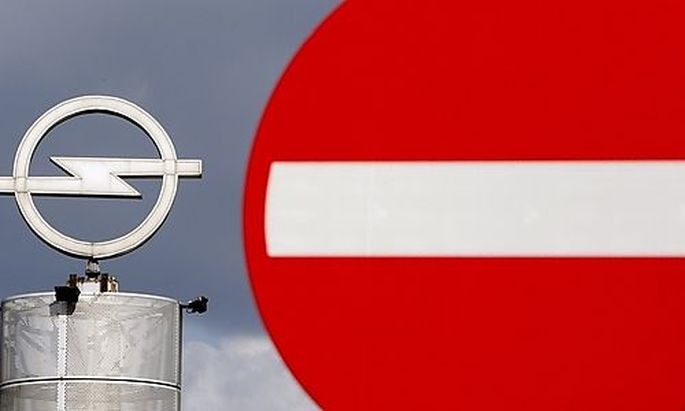 FILE - In this Thursday Sept. 10, 2009 file photo an Opel logo is seen next to a traffic sign outside