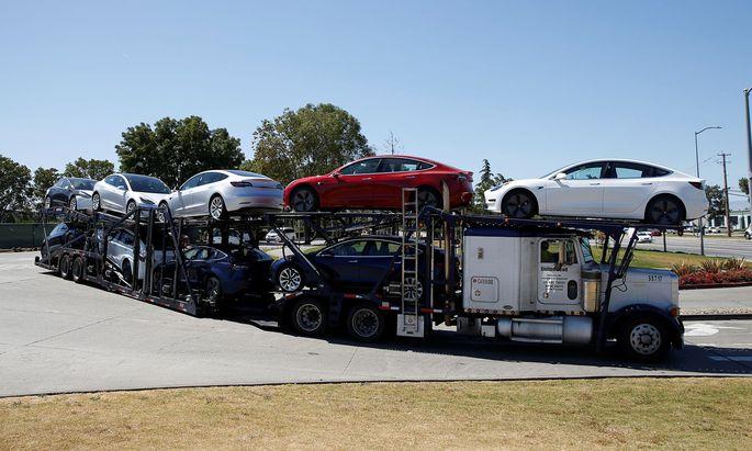 A car carrier trailer carries Tesla Model 3 electric sedans, is seen outside the Tesla factory in Fremont