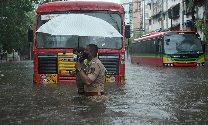 News Bilder des Tages May 17, 2021, Mumbai, India: A policeman helps a public transport driver to cross a flooded street