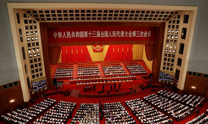 FILE PHOTO: Officials and delegates attend the opening session of NPC in Beijing
