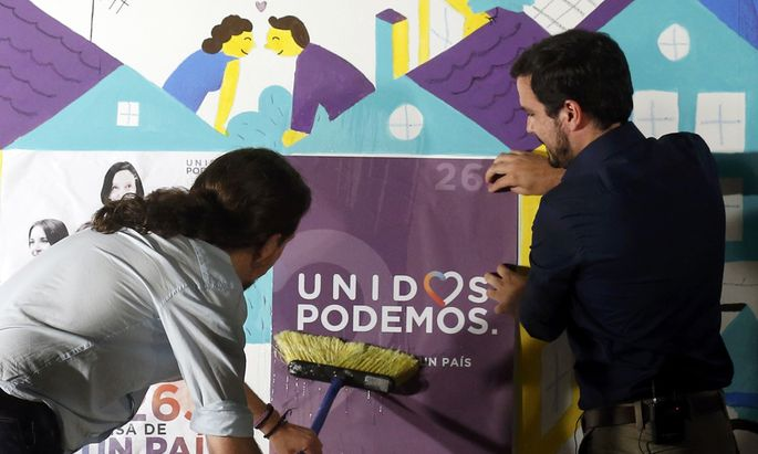 Podemos (We Can) leader Pablo Iglesias and Izquierda Unida (United Left) leader Alberto Garzon, of Unidos Podemos (United We Can) coalition, put up a campaign poster in Madrid