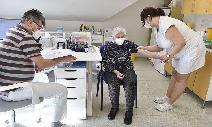 Doctor Jiri Bartos, left, and an elderly woman, center, who receives a vaccine against the covid-19, at the surgery off
