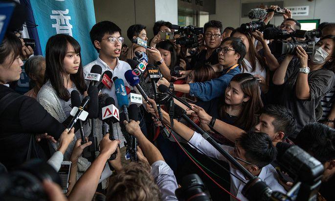 Joshua Wong war das Gesicht der Demokratieproteste 2014. Seine Verhaftung (und die seiner und Mitstreiterin Agnes Chow) dient zur Abschreckung. Stunden später sind Wong und Chow am Freitag wieder aus dem Polizeigebäude gegen Kaution entlassen worden.