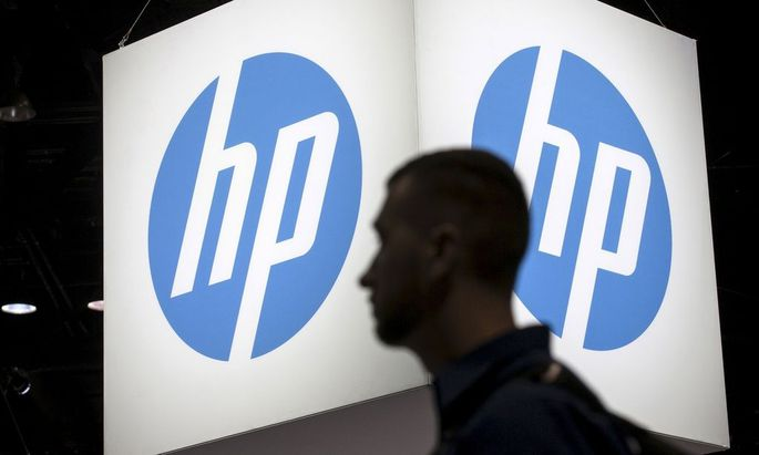 File photo of an attendee at the Microsoft Ignite technology conference walking past the Hewlett-Packard (HP) logo in Chicago, Illinois