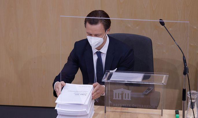 """Finanzminister Gernot Blümel (ÖVP) und der berüchtigte """"Budgetziegel"""": Der Voranschlag für 2022 umfasst 3400 Seiten und wiegt etwa zwölf Kilogramm."""