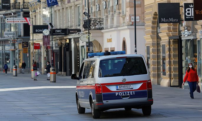 A police car drives next to closed shops in Vienna