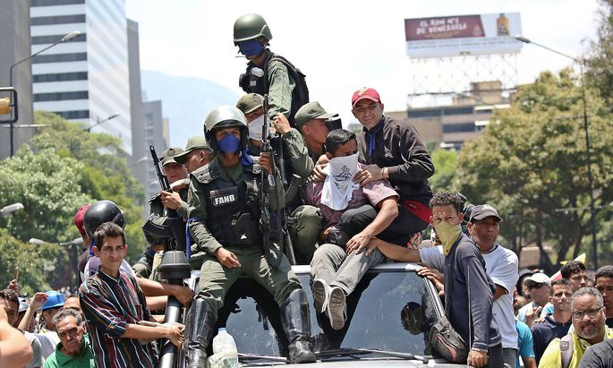 Soldiers ride on top of a car with supporters of Venezuelan opposition leader Juan Guaido during anti-goverment protests, in Caracas