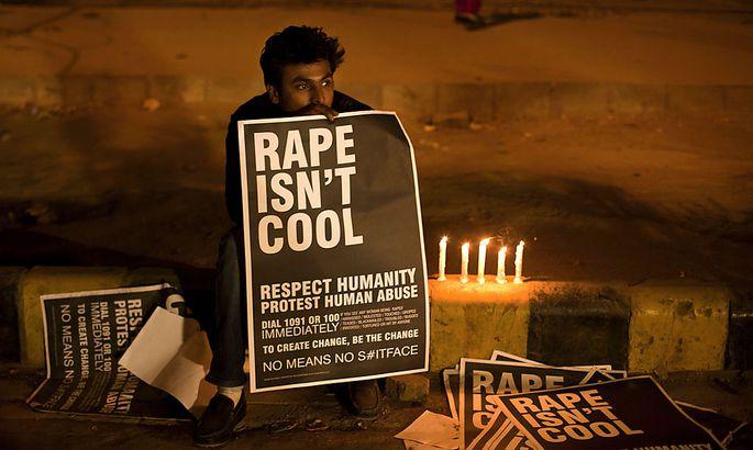 Ein Mann hält bei einer Totenwache für das Vergewaltigungsopfer ein Schil mit der Aufschrift