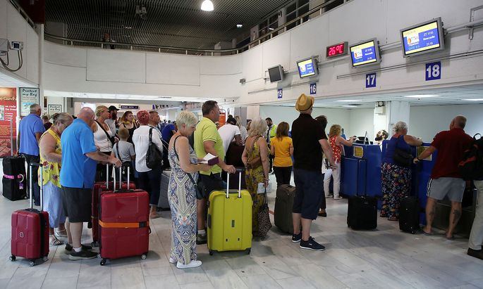 FILE PHOTO: Passengers line up in front of Thomas Cook counters at the airport of Heraklion, on the island of Crete