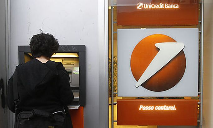 A woman uses an automatic teller at the UniCredit bank in Rome, Thursday, Jan. 5, 2012. Trading in Un