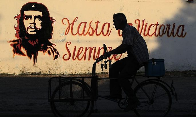 A graffiti of revolutionary character Ernesto 'Che' Guevara is seen on a wall as a men rides past on his tricycle in Havana