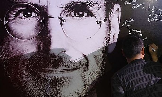 A man signs his name on a sympathy board set up for Steve Jobs Day in Manila