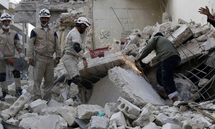 Civil Defence workers remove debris at a site hit by what activists said were barrel bombs dropped by forces loyal to Syria's President Assad in Aleppo