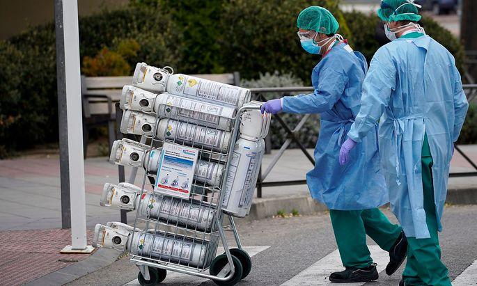 Ein Bild aus Madrid, wo Krankenhausmitarbeiter eine neue Lieferung Sauerstoffflaschen erhalten.