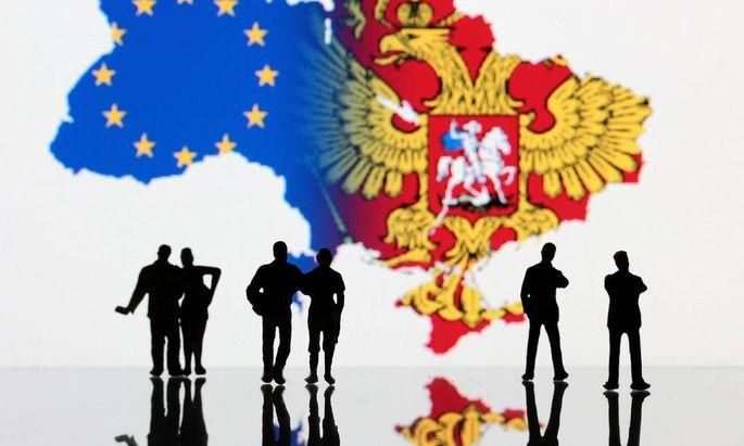 Symbolbild zur Krise in der Ukraine Personen stehen vor dem Umriss der Ukraine im Westen die Flagg