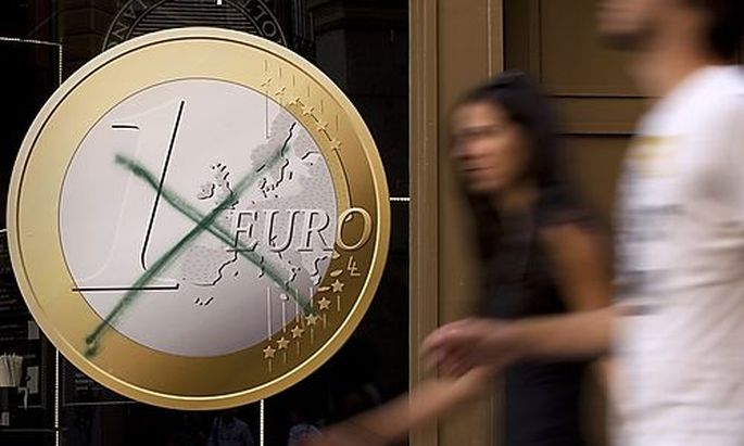 People walk past a pizza shop with a euro sign which was crossed out in central Madrid