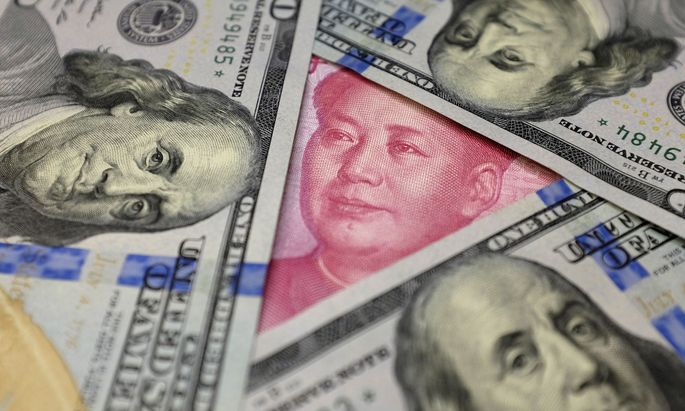 FILE PHOTO: U.S. 100 dollar banknotes and a Chinese 100 yuan banknote are seen in this picture illustration