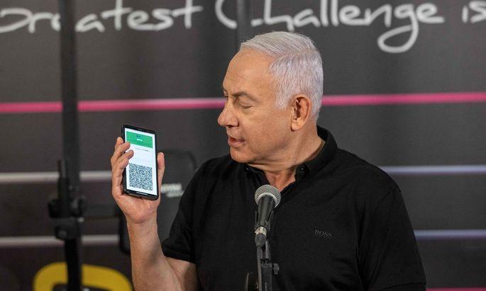 Israels Premier Benjamin Netanjahu spricht vor einem Fitnessstudio, das nun mit einem Grünen Pass wieder besucht werden darf.