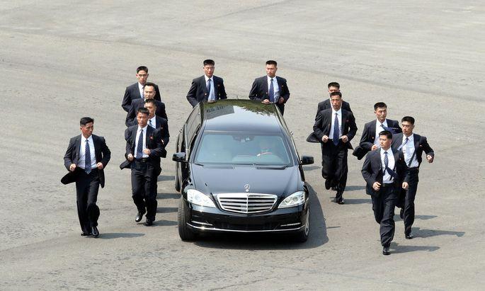 Kim Jong-uns Leibwächter eskortieren eine Limousine, die der nordkoreanische Diktator eigentlich gar nicht besitzen dürfte: einen Mercedes-Maybach S 600.